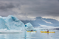 Sea kayaking among icebergs in Bear Glacier Lagoon, Kenai Fjords National Park, southcentral, Alaska.