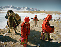 Every morning, the girls from the Khan's camp are in charge of getting water all throughout winter in sub zero temperature. They have to dig hole in the ice to hope and find the spring that always freezes overnight..Qyzyl Qorum campment, Abdul Rashid Khan's camp (leader of the Afghan Kyrgyz). .Winter expedition through the Wakhan Corridor and into the Afghan Pamir mountains, to document the life of the Afghan Kyrgyz tribe. January/February 2008. Afghanistan