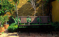 A three seater wooden bench sits in the corner of a courtyard garden