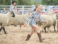 Attending her first rodeo, Camilla Johnson, 7, of River Falls wake away triumphantly after riding  a sheep Saturday, September 14, 2013, during the mutton busting portion of the Falcon Frontier Days Rodeo. Johnson's was the last ride out of all the children participating, and the longest to stay on.