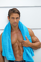 portrait of a very handsome muscular man with blue eyes and brown hair with a blue towel around his neck