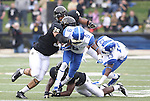 UK wide receiver Demarco Robinson gets tackled by Vanderbilt defenders during the first half of the University of Kentucky vs. Vanderbilt University football game at Vanderbilt Stadium in Nashville, Tenn., on Saturday, November 16, 2013. Vanderbilt won 22-6. Photo by Tessa Lighty | Staff