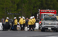 Mar 14, 2015; Gainesville, FL, USA; NHRA top fuel dragster driver Larry Dixon (center) walks to an ambulance with members of the safety safari after his car broke in half during qualifying for the Gatornationals at Auto Plus Raceway at Gainesville. Dixon walked away from the incident. Mandatory Credit: Mark J. Rebilas-