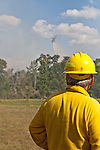 Lee Bentley from northern California watches as an aerial fire fighting helicopter drops retardant on the Dyer Mill fire in Grimes County, Texas on June 21, 2011.