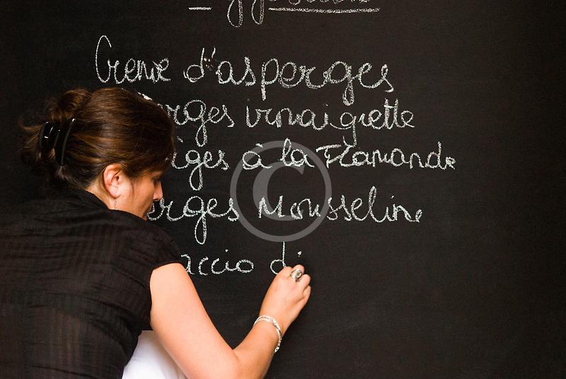 Belgium, Brussels, Woman writing menu on chalk board