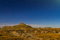 Stars of summer (Ophiuchus) setting in the southwest over the badlands of Dinosaur Provincial Park, Alberta, with the landscape illuminated by light from the nearly Full Moon. This is a single 13-second exposure at f/2.8 and ISO 400 with the Canon 7D and 24mm lens.