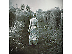 A woman dressed in a long vintage outfit, walking along a path in the garden.
