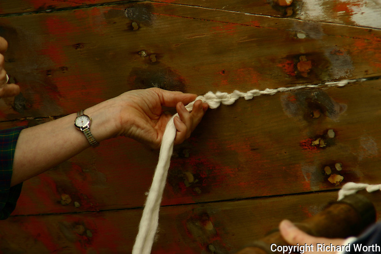 Using a caulking mallet and caulking iron, Joan Madson drives the caulking fabric into the seams of thls boat being restored near Half Moon Bay, California.