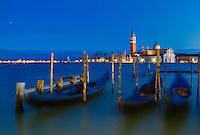 Gondolas moored by Saint Mark square with San Giorgio di Maggiore church in the background. Venice, Italy.
