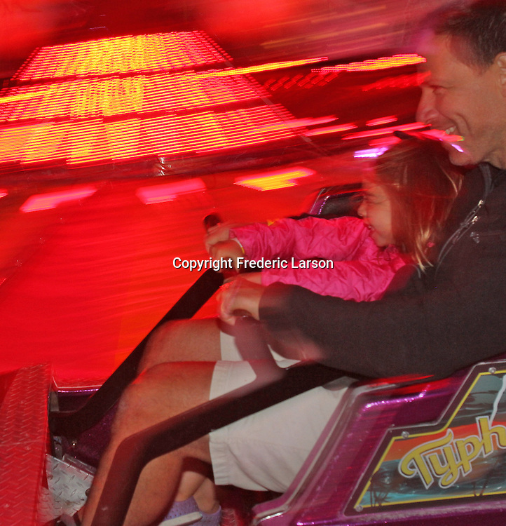 A father daughter enjoy a roller coaster ride at the Mill Valley carnival during Memorial Day Weekend.