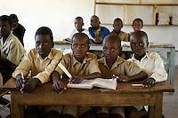Children share a book in a government-run school.