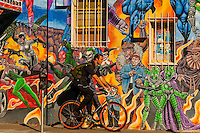 "An urban bicyclist riding down the sidewalk with a mural of comic book super heroes on the side of ""Masks Y Mas"" store in background, Albuquerque, New Mexico USA"
