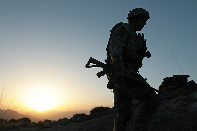 As dawn breaks, Staff Sgt. Jason Gregory, 29, of San Antonio, Texas, a soldier with Company A, 2nd Battalion, 503rd Parachute Infantry Regiment, walks to the temporary command post atop a mountain in the Narang valley, in Kunar province, Afghanistan. Gregory and other soldiers were protecting a team during a two-day mission to direct air and artillery strikes on Taliban positions in the valley below. May 17, 2008. DREW BROWN/STARS AND STRIPES