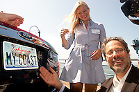 Santa Monica Mayor Richard Bloom and actress/Heal the Bay Board Member Amy Smart <br /> affix the new Whale Tail&reg; license plate to a Ford Fusion from Santa Monica Ford following The California Coastal Commission and the Department of Motor Vehicles' press conference debuting the new specialty license plate at the Santa Monica Pier on Tuesday, Aug 2, 2011.