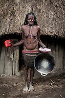 Uma Mabel, 49, holds plastic 'made-in-China' dishes, which she bought in the local market for about 120,000 Rupiah (GBP 6.34). She says that four years ago her family kept using traditional handmade household staff.<br /> Anemaugi village, West Papua Province.