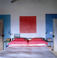 A simple mural in red and blue has been painted on the wall behind the bed in this simple bedroom