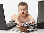 Six month old baby boy busy with computers and cell phones