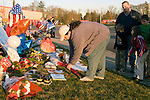 Angie Corey (L) lays flowers as her husband Gordon, a former police officer,  and their three children (FL) Coery, Maddie and Steven pay their respects at a memorial of flowers, balloons, and wreaths for four slain police officers at the Forza Coffee Shop  in Lakewood, Washington, USA, on 2 December  2009. Four Lakewood officers were gunned down during a morning meeting at a local coffee shop on 29 November 2009. Jim Bryant Photo. ©2010. ALL RIGHTS RESERVED.