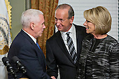 Dick DeVos Jr., center, shakes hands with United States Vice President Mike Pence after swearing in Betsy DeVos, U.S. Secretary of Education, right, in the Vice President's Ceremonial Office in Washington, D.C., U.S., on Tuesday, Feb. 7, 2017. DeVos squeaked through a history-making Senate confirmation vote to become U.S. education secretary, as Vice President Mike Pence broke a 50-50 tie and Republicans staved off last-minute defections that would have killed her nomination. <br /> Credit: Andrew Harrer / Pool via CNP