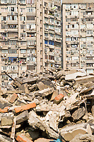 Rubble of demolished building with apartments in background, Shanghai, China