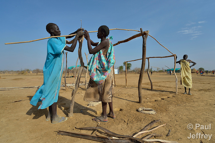 Women construct a shelter in the internally displaced persons camp in Turalei, South Sudan. Families started arriving here shortly after fighting broke out in December 2013, and new families continued to arrive in March 2014 as fighting continued. Many are living in the open and under trees. The ACT Alliance is providing the displaced families and the host communities affected by their presence with a variety of support, including new wells.