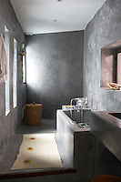 This minimal bathroom has a tadelakt bath, a traditional form of Moroccan plaster