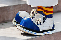 A clown wears oversized blue and white shoes during the Clown Congress in San Salvador, El Salvador, 18 May 2011. The clown performance is considered a regular job in most of Latin American countries. Clowns may work individually or in groups, often performing advertisement like acts in large open-to-street shops or they take part in private shows, like children birthdays, family events etc. There are many clown conventions all over Latin America where clowns gather and exchange their experiences offering workshops of the comic acting or the art of make-up. For some of them, being clown is a serious lifetime profession.