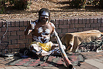Australian Aborigine giving a thumbs up sign and smiling at the camera holds a Didgeridoo