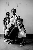 31 years old Suthakaran Shanthirakala poses for  photo with her children and the CHDR- Child Health Development Record Card (immunization/vaccination card) in Punaineeravi Village in Kilonochchi, Sri Lanka.  Photo: Sanjit Das/Panos