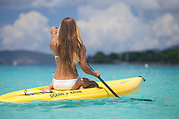 Woman kneeling on a stand up paddle board.VI  Eco Tours.Honeymoon Beach, St. John.U.S. Virgin Islnads