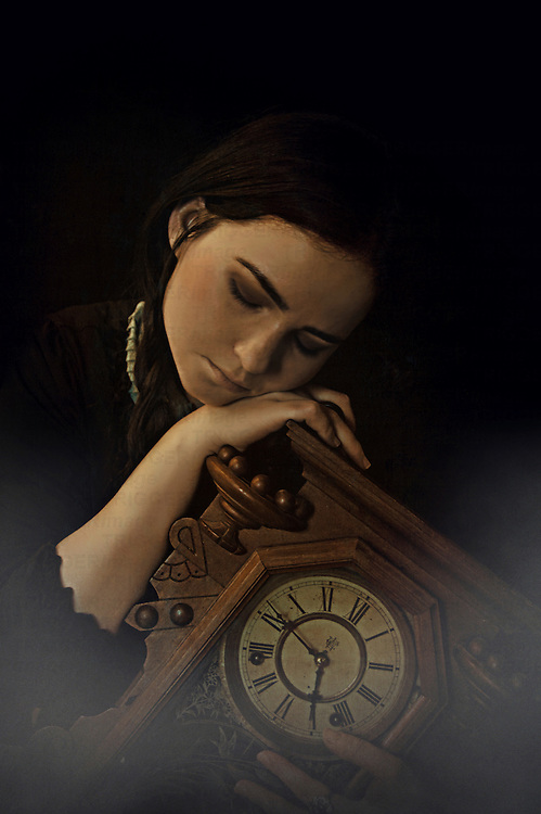 Photograph of a young woman with dark hair and makeup clutching onto a wooden antique clock. She is laying her head on her hand looking distresed or hopeful. The clock is from Germany and is over 100 years old. It enables the owner to travel back in time just once.