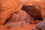 A visitor enjoys Sand Dune Arch in Arches National Park, Utah