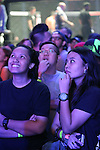 Two young women watch the video screens ecstatic as heroes battle it out in the ring<br />