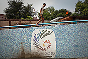 A young boy walks over the wall of an underpass leading to the Tyagaraja stadium for the approaching 19th Commonwealth Games 2010 in New Delhi, India.