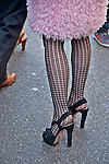 Woman in a vintage pink coat and black heels in the Easter Parade on Fifth Avenue in New York City