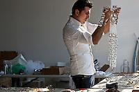 Jeweler to the stars Rodrigo Otazu examines a piece of his artwork during a photo shoot in New York, 8 November 2009.