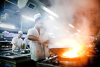Smoke and flames rise from a wok as a chef prepares a dish in one of The West Lake Restaurant's kitchens. Able to seat up to 5,000 people at one sitting, The West Lake Restaurant is the biggest Chinese restaurant in the world. Each week its diners, who staff are taught are 'the bringers of good fortune', devour 700 chickens, 200 snakes, 1,200 kgs of pork and 1,000 kgs of chillis. Its 300 chefs cook in five kitchens and its staff total more than 1,000.It is fully booked most nights.