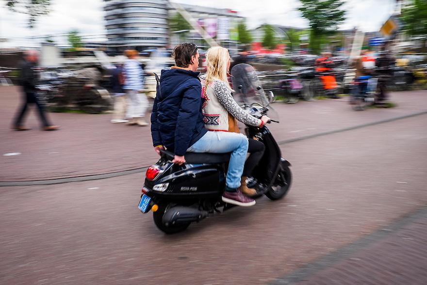 Nederland, Amsterdam, 30 mei 2015<br /> Snorscooter in het centrum van de stad.  Scooters stoten veel fijn stof uit en zijn enorm ongezond voor de stadsbewoners. De luchtkwaliteit wordt ernstig aangetast door scooters en bromfietsen of snorfietsn. Scooters irriteren veel verkeersdeelnemers omdat ze zich vaak niet aan de verkeersregels houden en hard en a-sociaal rijden.<br />  <br /> Foto: Michiel Wijnbergh