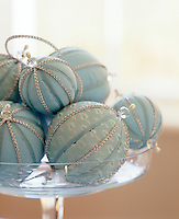 Handmade baubles decorated with silver strings and crystals on pale blue taffeta