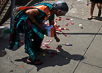 A woman picks up an American flag while she attends the annual Indian independence day parade in New Jersey,  August 11, 2013. Photo by Eduardo Munoz Alvarez / VIEWpress.