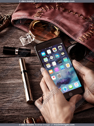 Woman hands holding Apple iPhone 7 Plus with her purse, makeup and accessories on the table conceptual still life