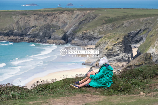 A tourist rests and enjoys the spectacular views at Carnewas at Bedruthan in Cornwall.