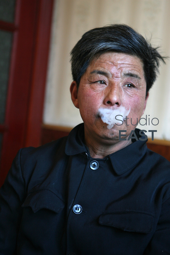We met this farmer on a small town and he told us about his life while smoking cigarettes. Then he brought us to his farm in the remote village of Yongfu, on February 27, 2006. Photo by Lucas Schifres/Pictobank