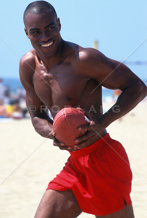 Shirtless young man on the beach enjoying a game of football