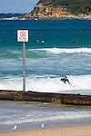 Manly Beach, New South Wales, Australia; pipeline with posted contaminate warning signs with surfers in the background © Matthew Meier, matthewmeierphoto.com All Rights Reserved