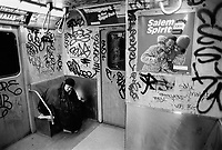 USA. New York City. Old homeless woman in the subway. Graffiti. Advertisement for Salem cigarettes. Company Campaign: Salem Shows Spirit. The R. J. Reynolds Tobacco Company (RJR) is an indirect wholly owned subsidiary of Reynolds American Inc. which in turn is 42% owned by British American Tobacco. 15.02.86 © 1986 Didier Ruef