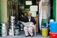 Pakistani retailer sits reading newspaper in village of Pattika, Pakistan