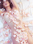 Sensual romantic portrait of a beautiful nude asian woman lying in bed with pink rose petals covering her naked body