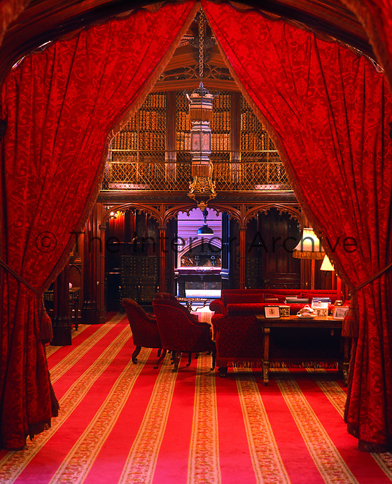 The entrance to the magnificent gothic library is framed by heavy curtains in a deep red damask