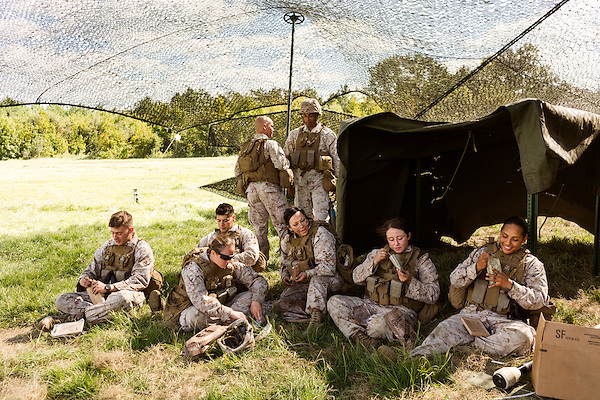 October 22, 2014. Camp LeJeune, North Carolina.<br />  Marines of artillery Battery A of the Ground Combat Element Integrated Task Force, including (right to left) LCpl. Christine Ruperto, Cpl. Angelique Preston and Pfc. Livier Vielehr, break for chow after camouflaging their trucks and howitzers.  The women in the unit have the MOS of field artillery cannoneer (0811), a job previously closed to female Marines.<br /> The Ground Combat Element Integrated Task Force is a battalion level unit created in an effort to assess Marines in a series of physical and medical tests to establish baseline standards as the Corps analyze the best way to possibly integrate female Marines into combat arms occupational specialities, such as infantry personnel, for which they were previously not eligible. The unit will be comprised of approx. 650 Marines in total, with about 400 of those being volunteers, both male and female. <br />  Jeremy M. Lange for the Wall Street Journal<br /> COED